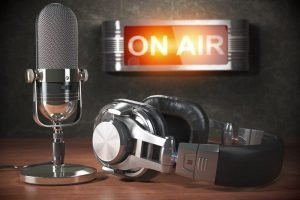 Vintage-microphone-and-headphones-with-signboard-on-air-800x533