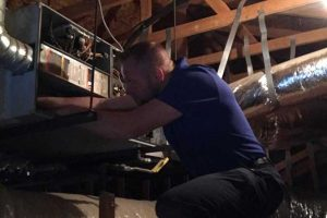 Mark working on an air system in an attic